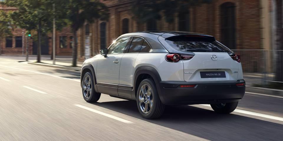 A white 2022 Mazda MX-30 driving down a city street.