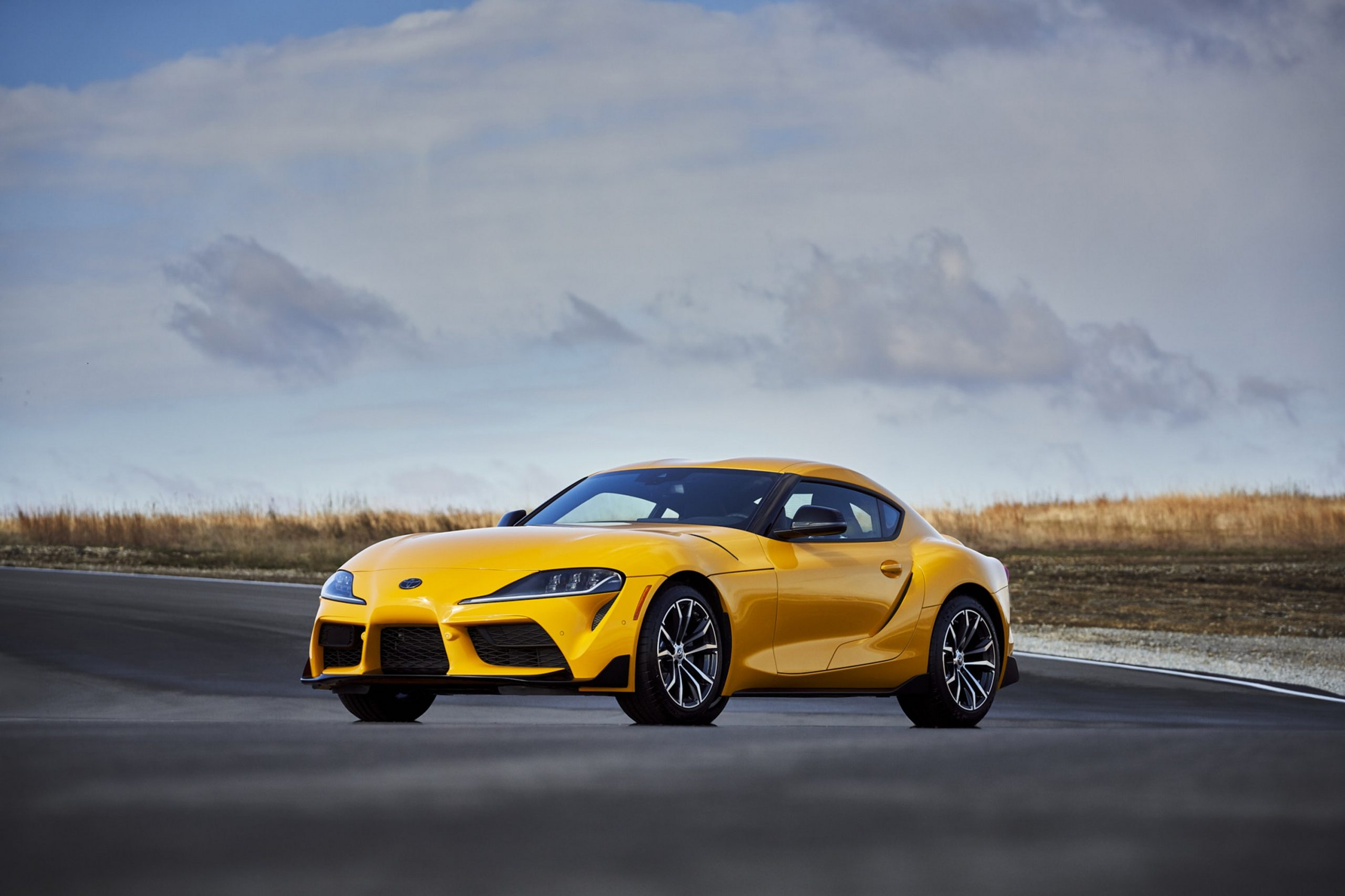 A yellow 2022 Toyota Supra 2.0 shot from the 3/4 angle on a racetrack