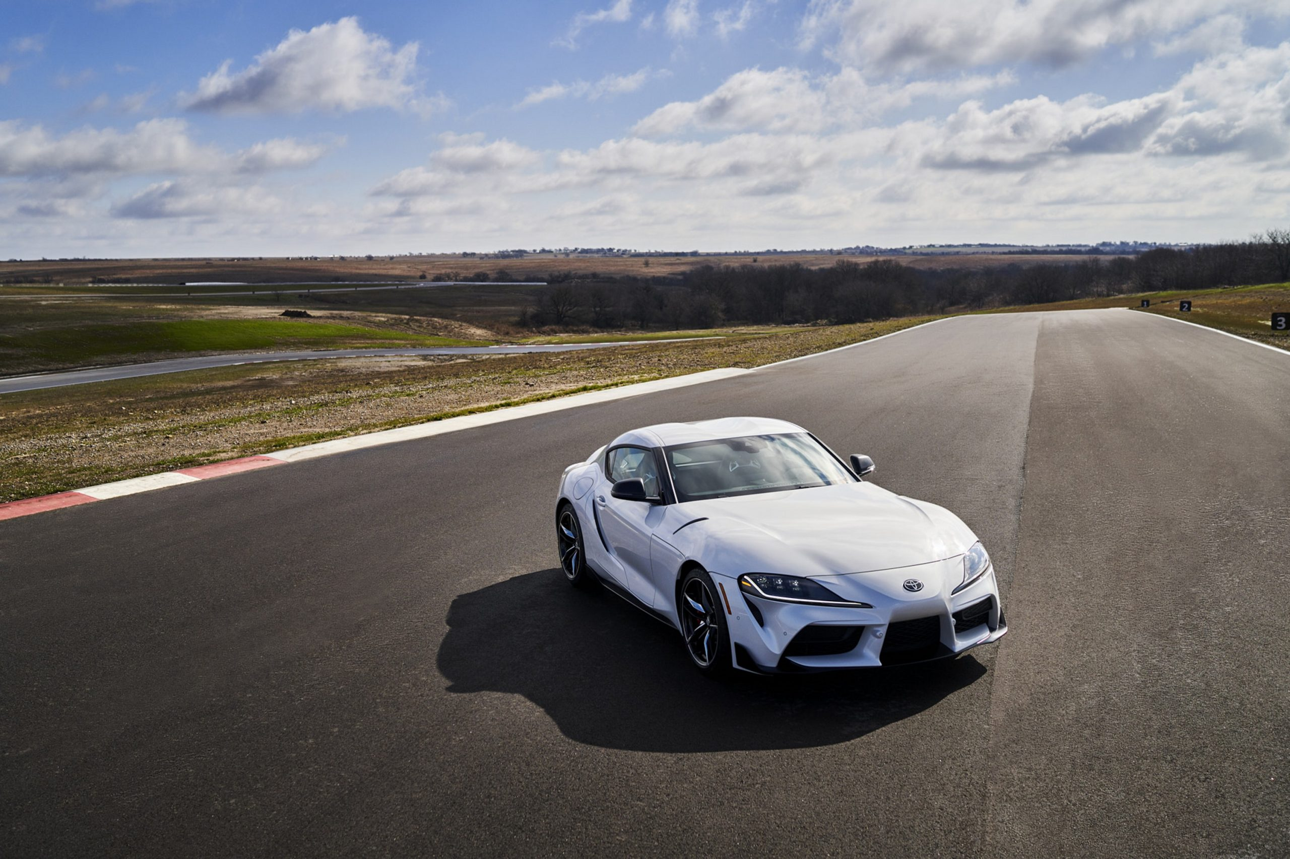 A white Toyota Supra 3.0 Premium shot on a racetrack from the high 3/4 angle