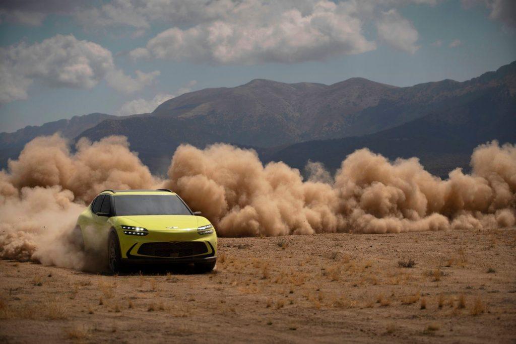A yellow-green 2023 Genesis GV60 drives through the dirt