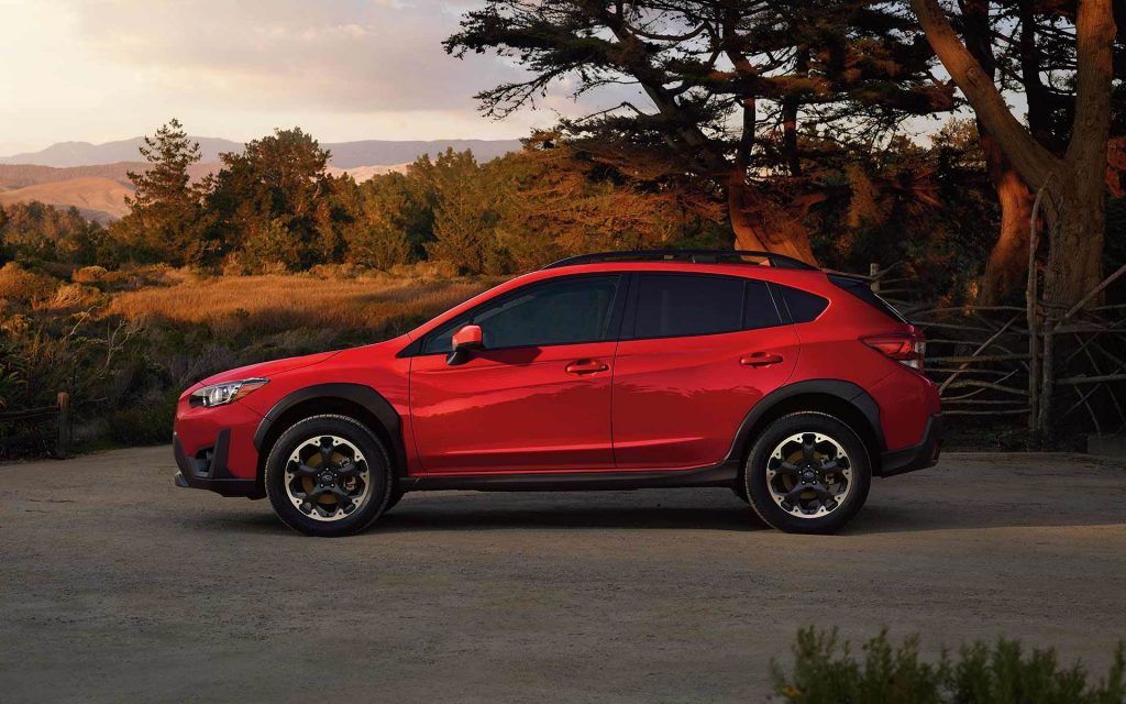 A red 2021 Subaru Crosstrek parked in front of mountains at sunset.