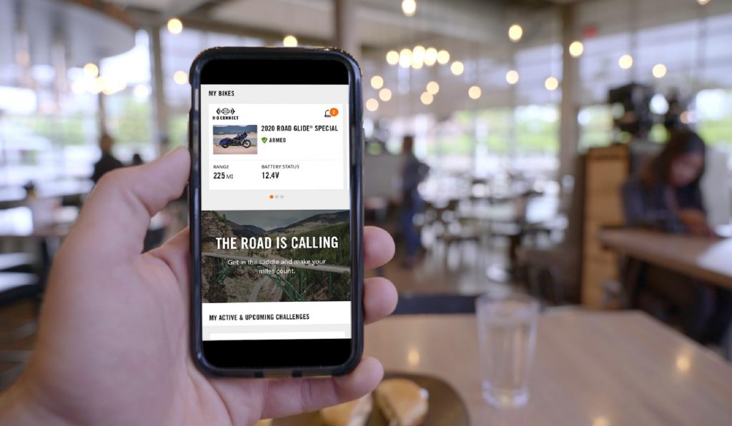 A 2020 Harley-Davidson Road Glide Special motorcycle rider accessessing the Harley-Davidson App on their smartphone