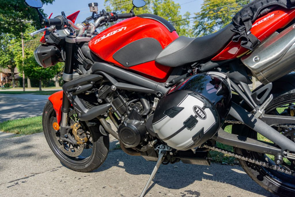 A black-and-white Bell motorcycle helmet locked to a red 2012 Triumph Street Triple R with a Kuryakyn lock