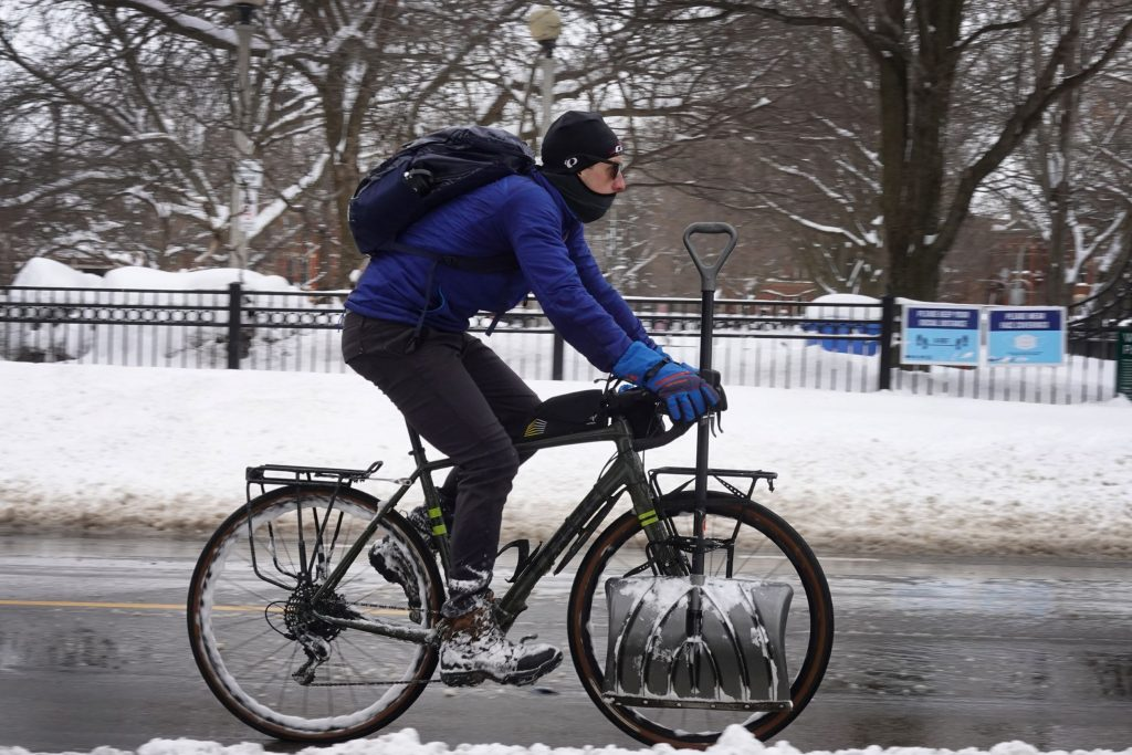 A Chicago cyclist with a shovel rides down the street dressed in winter cycling gear