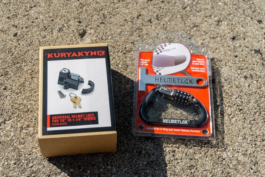 A black Kuryakyn motorcycle helmet lock in its box next to a black Helmetlok lock
