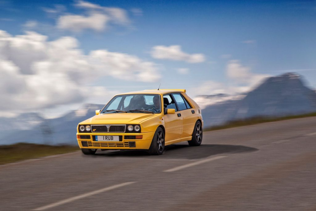 A yellow Lancia Delta Integrale drives through the French Alps