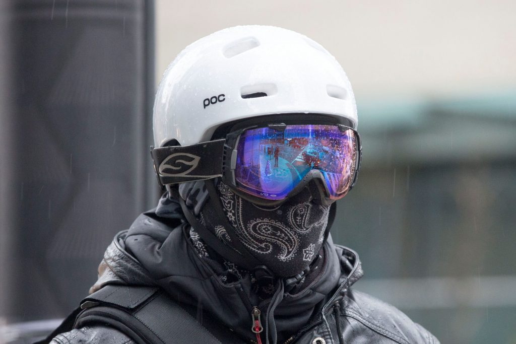 A black-clad cyclist wearing blue-tinted goggles and a black face covering for winter cycling