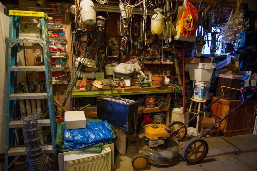 A silver lawn mower in storage in a garage
