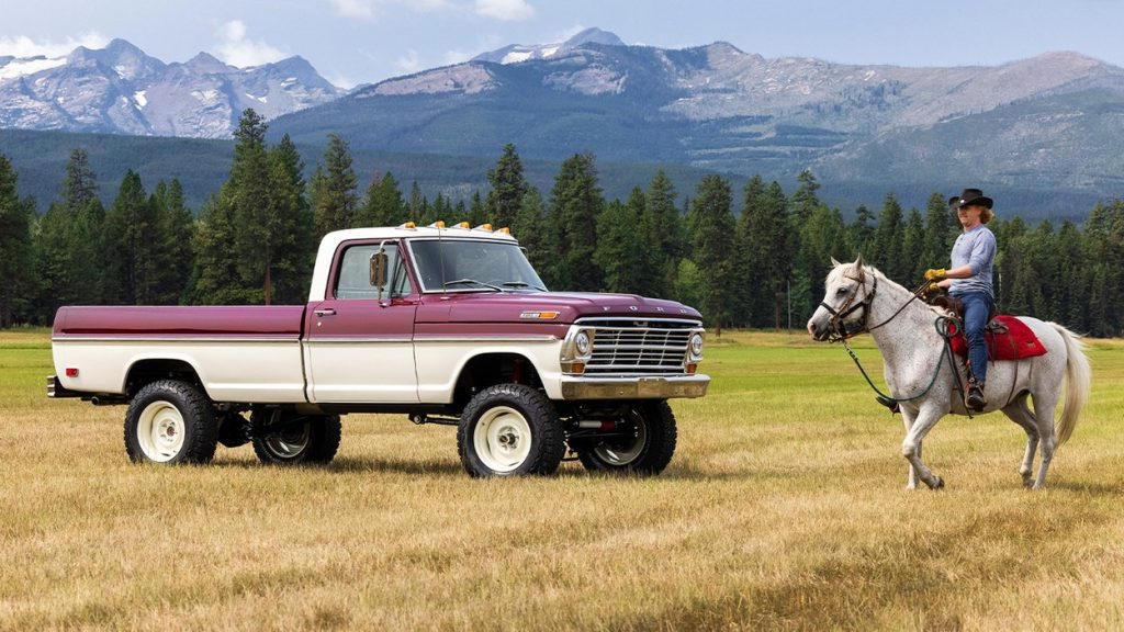 A man riding a horse by a vintage 1969 Ford F-100 truck