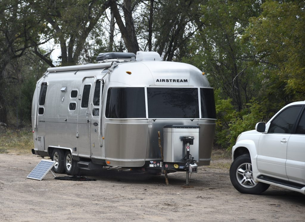 An Airstream Safari travel trailer with a solar panel kit parked in Ojo Caliente, New Mexico