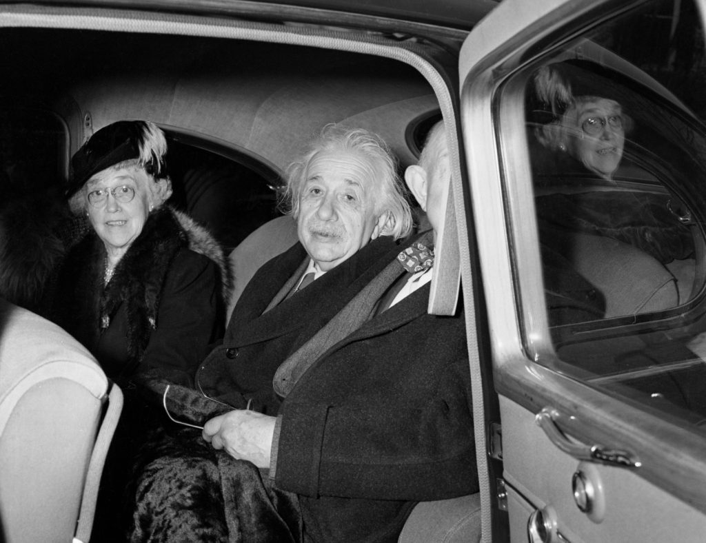 Albert Einstein in a car with his wife and another man