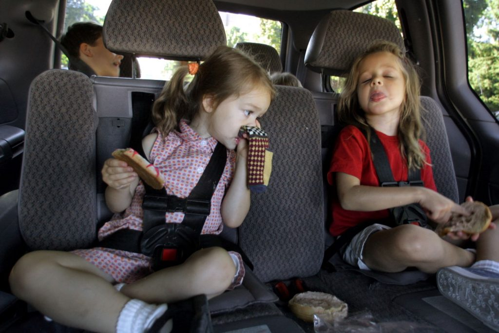 Children backseat of a car making a bad smell expression
