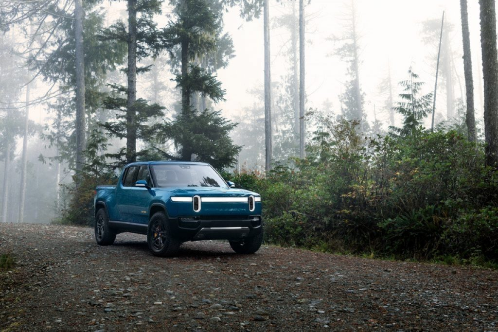 Blue Rivian R1T parked in a forest