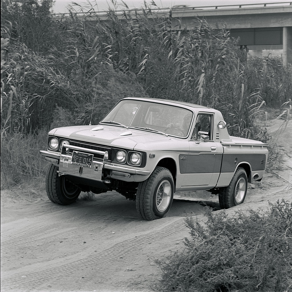 A Chevrolet LUV pickup truck driving off-road near tall grass