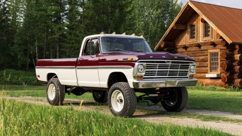 Classic 1969 Ford F-100 truck parked in front of a log cabin