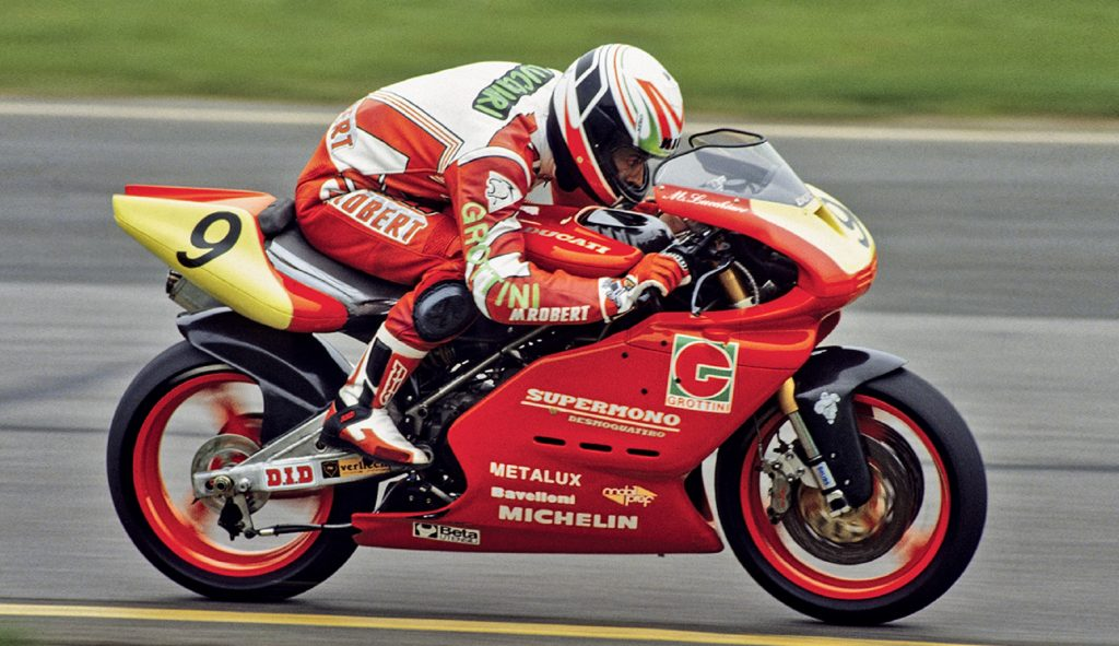 A rider racing a red-and-yellow Ducati Supermono