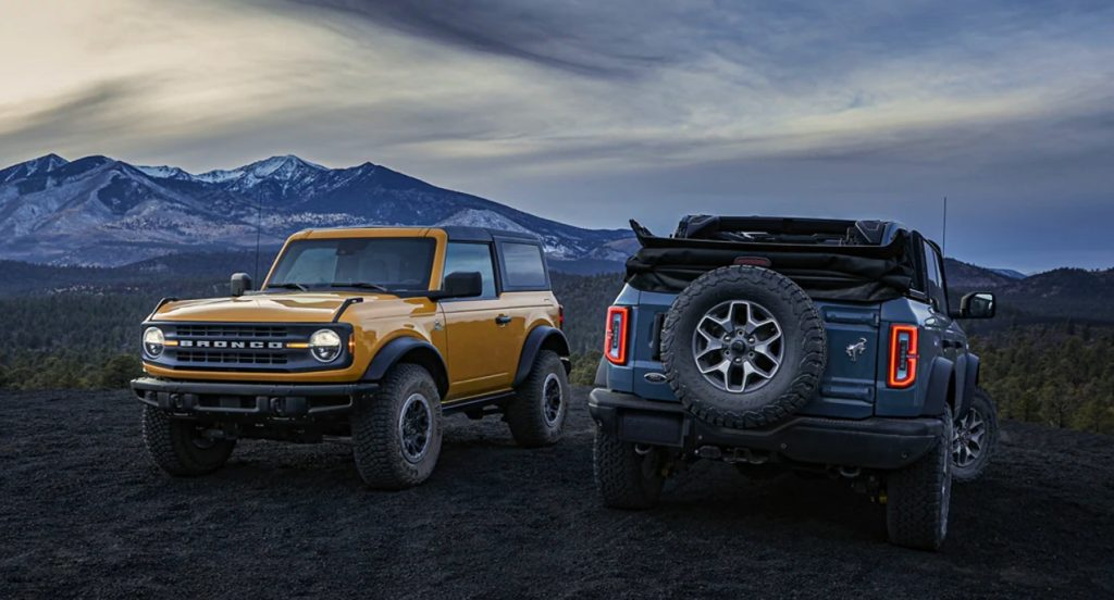 A yellow and a blue Ford Bronco are parked off-road.