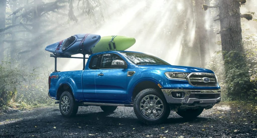 A blue 2022 Ford Maverick is parked in nature carrying kayaks.