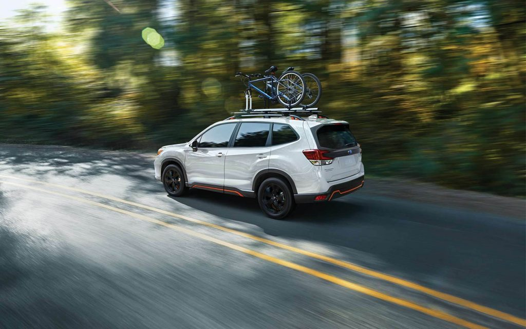 A white 2021 Subaru Forester speeding down a tree-lined road.