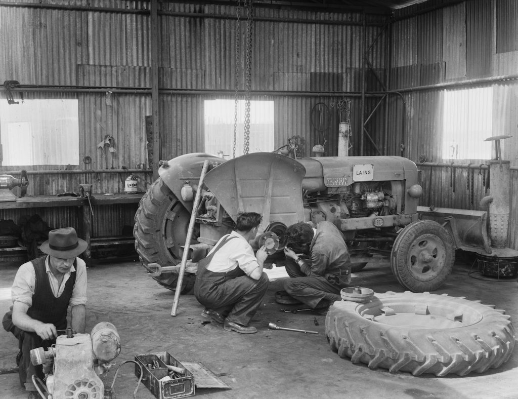 A view of two Laing workers carrying out maintenance work on the rear right wheel of a Fordson Major Diesel Tractor. Slow leaks have always been an annoying problem, but you can use soap to find a slow tire leak or valve stem leak.   Hulton Archive/Getty Images