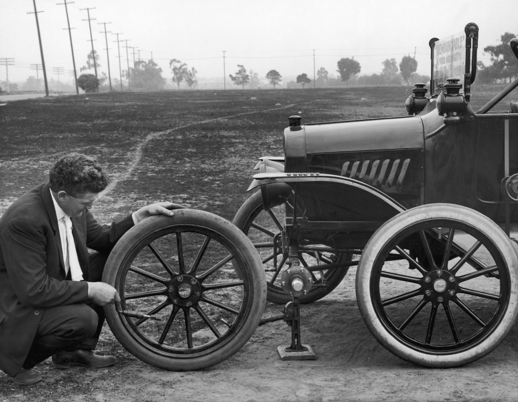 A man kneels outdoors to change the front tire on his Model 'T' Ford in 1915. He is demonstrating one of the first models with replaceable tires. Slow leaks have always been an annoying problem, but you can use soap to find a slow tire leak or valve stem leak.   Camerique Archive/Getty Images