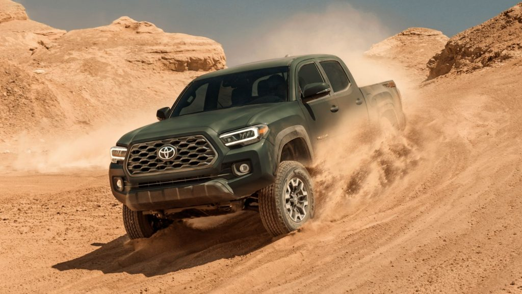 Green 2022 Toyota Tacoma driving down a sandy hill