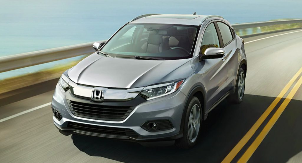 A silver Honda HR-V is driving on the road.