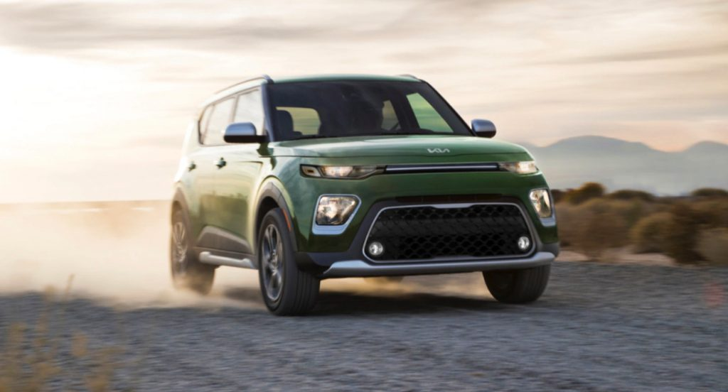 A green 2022 Kia Soul is driving on the road.