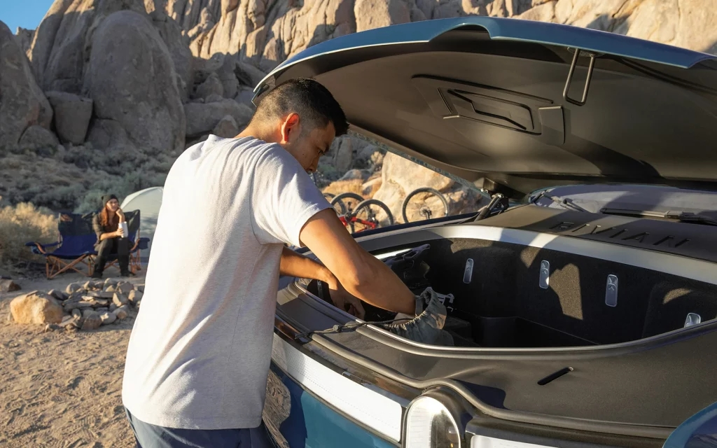 Man getting his gear from the frunk of a blue Rivian R1T