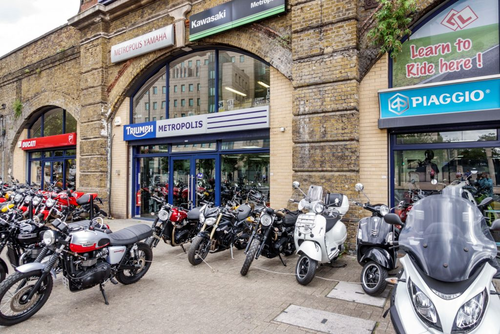 New and used Ducati and Triumph motorcycles and Piaggio scooters in front of a London dealer