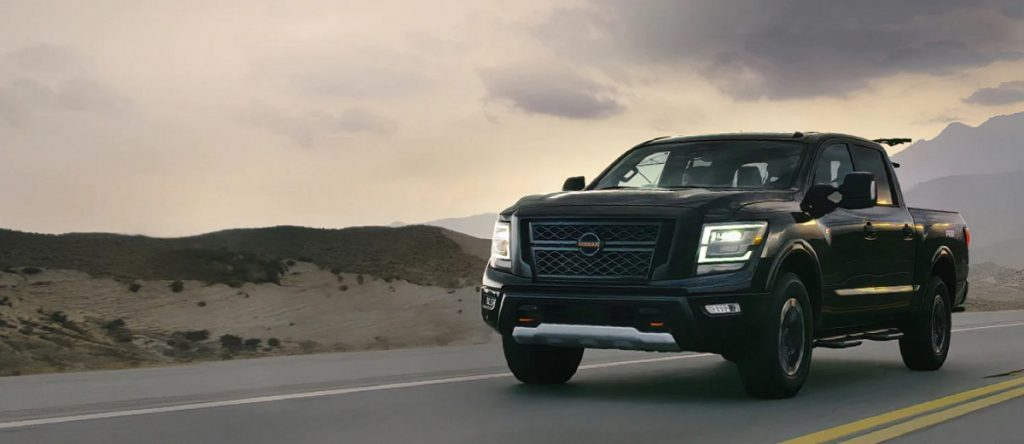 A black 2021 Nissan Titan driving past the mountains.