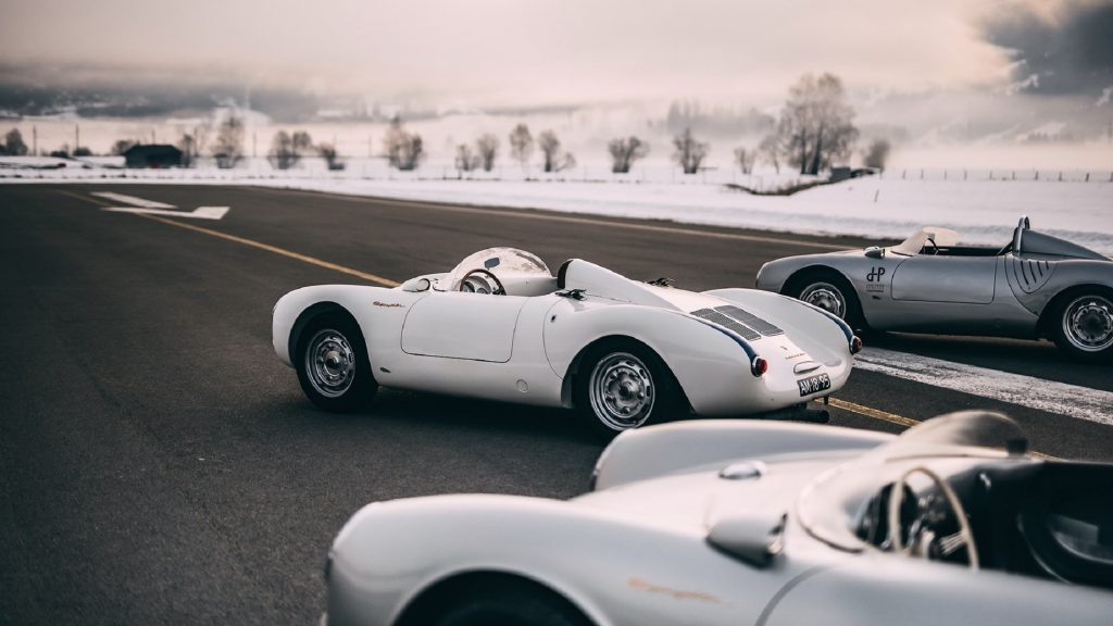 The rear side 3/4 view of several white and silver Porsche 550 Spyders on an Austrian runway