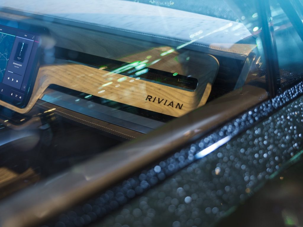 This is a promo photo of The Rivian Interior In The R1T Electric Pickup, in the rain | Rivian