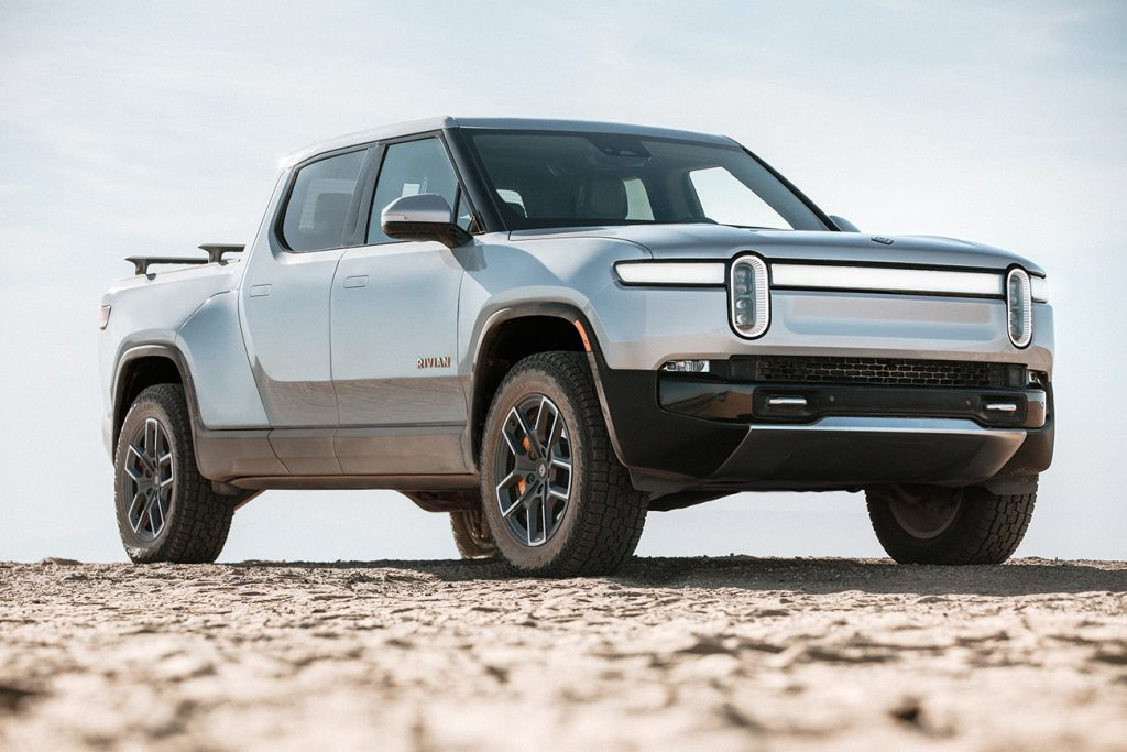 Rivian R1T electric truck in silver, parked on hill crest with dirt on tires