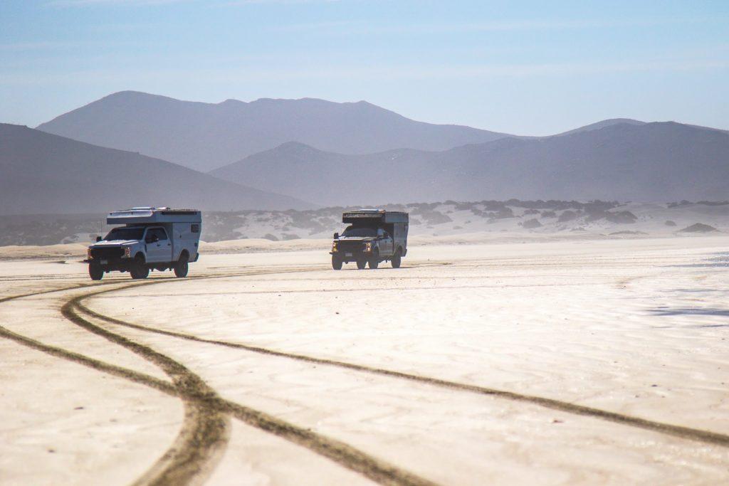 Two camper trucks driving through the desert