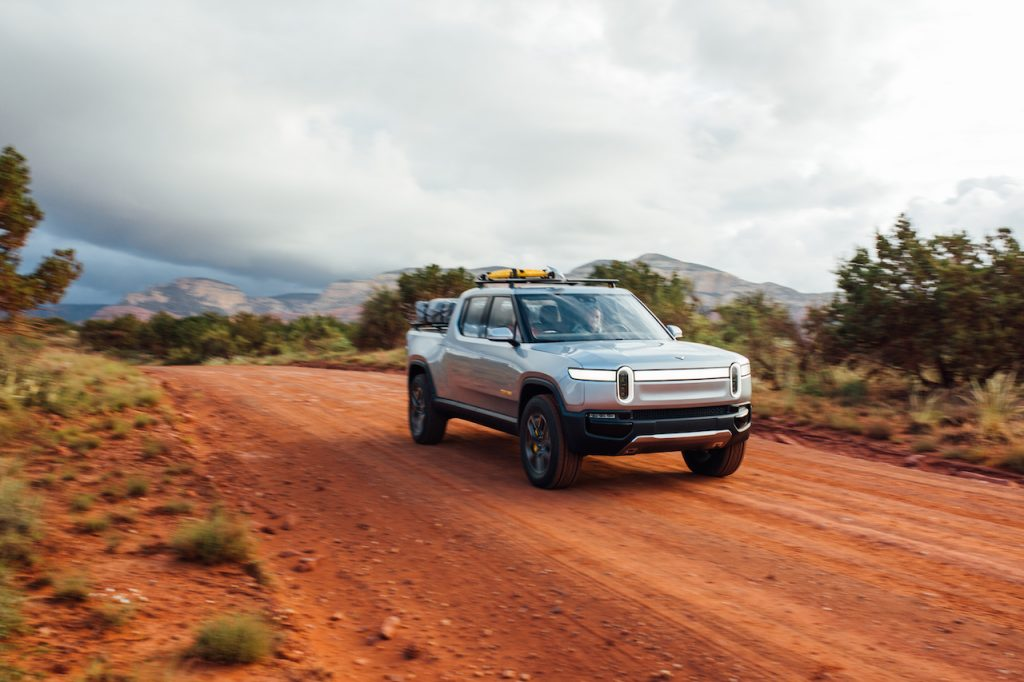 Silver Rivian R1T electric truck driving on a dirt road