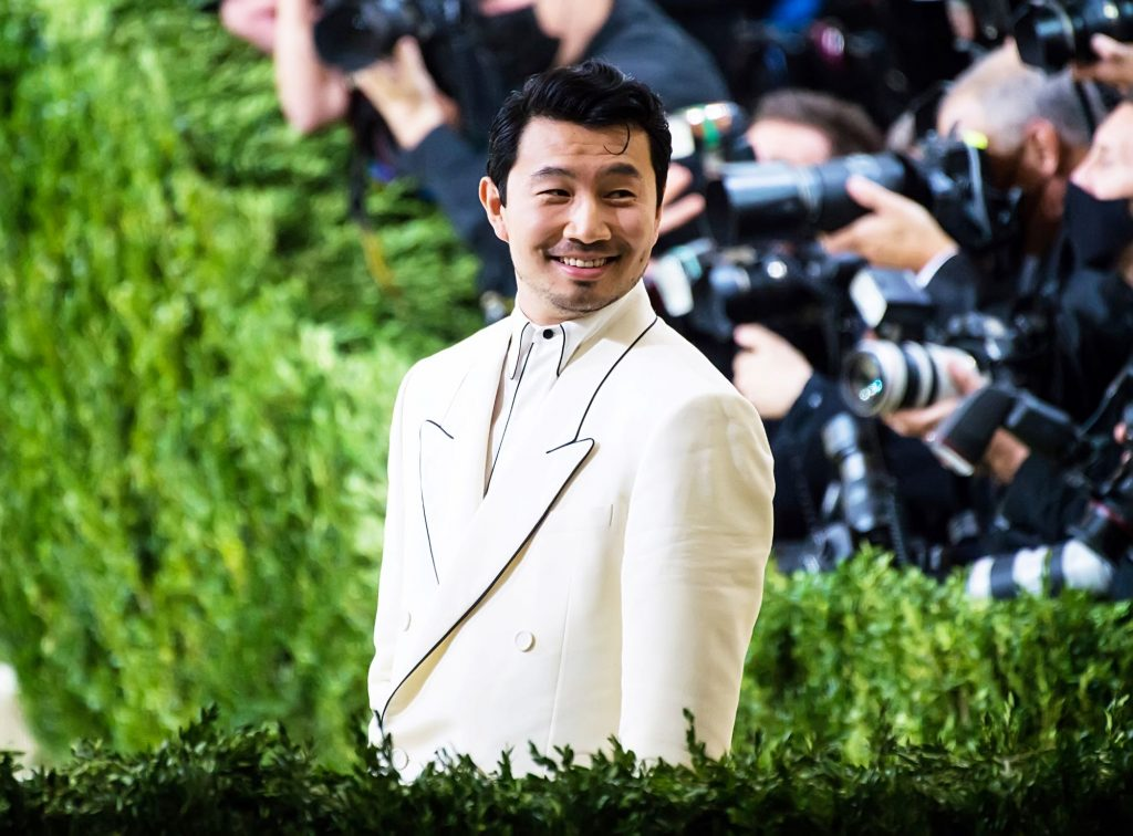 Simu Liu in a white suite with photographers in the background surrounded by shrubbery.