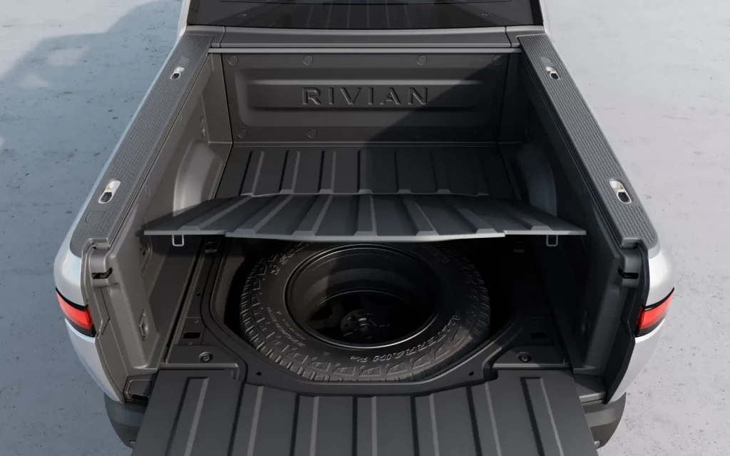 Spare tire under the pickup bed of a silver Rivian R1T