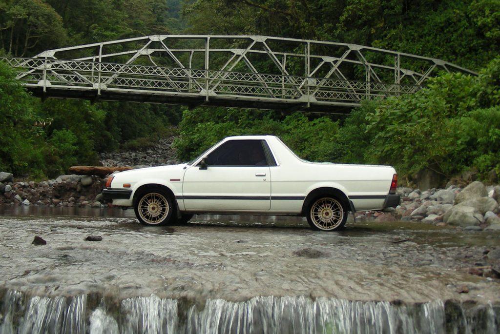 A white Subaru Brat parked near a bridge