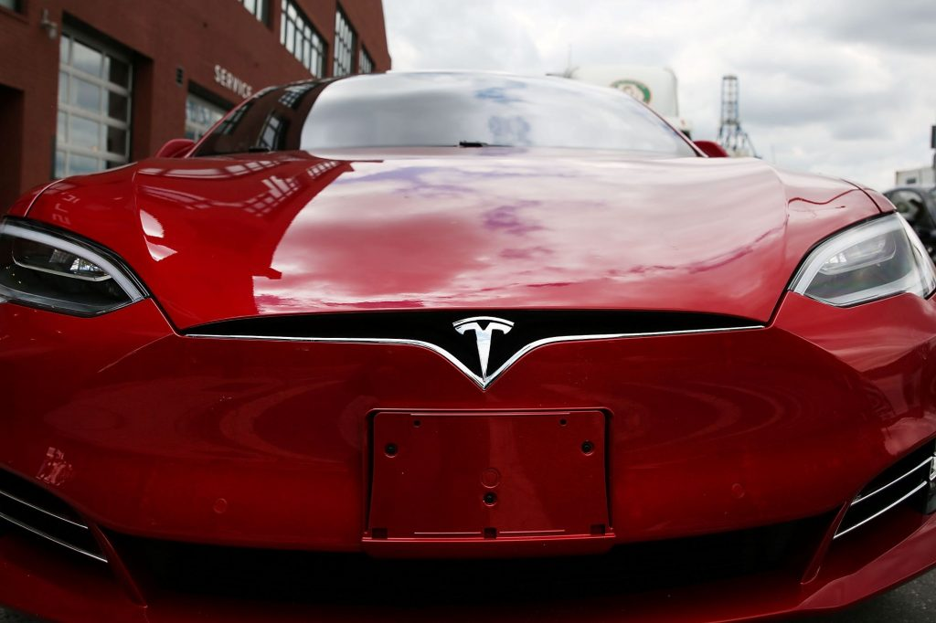 Red front of a Tesla using a wide angle lens.
