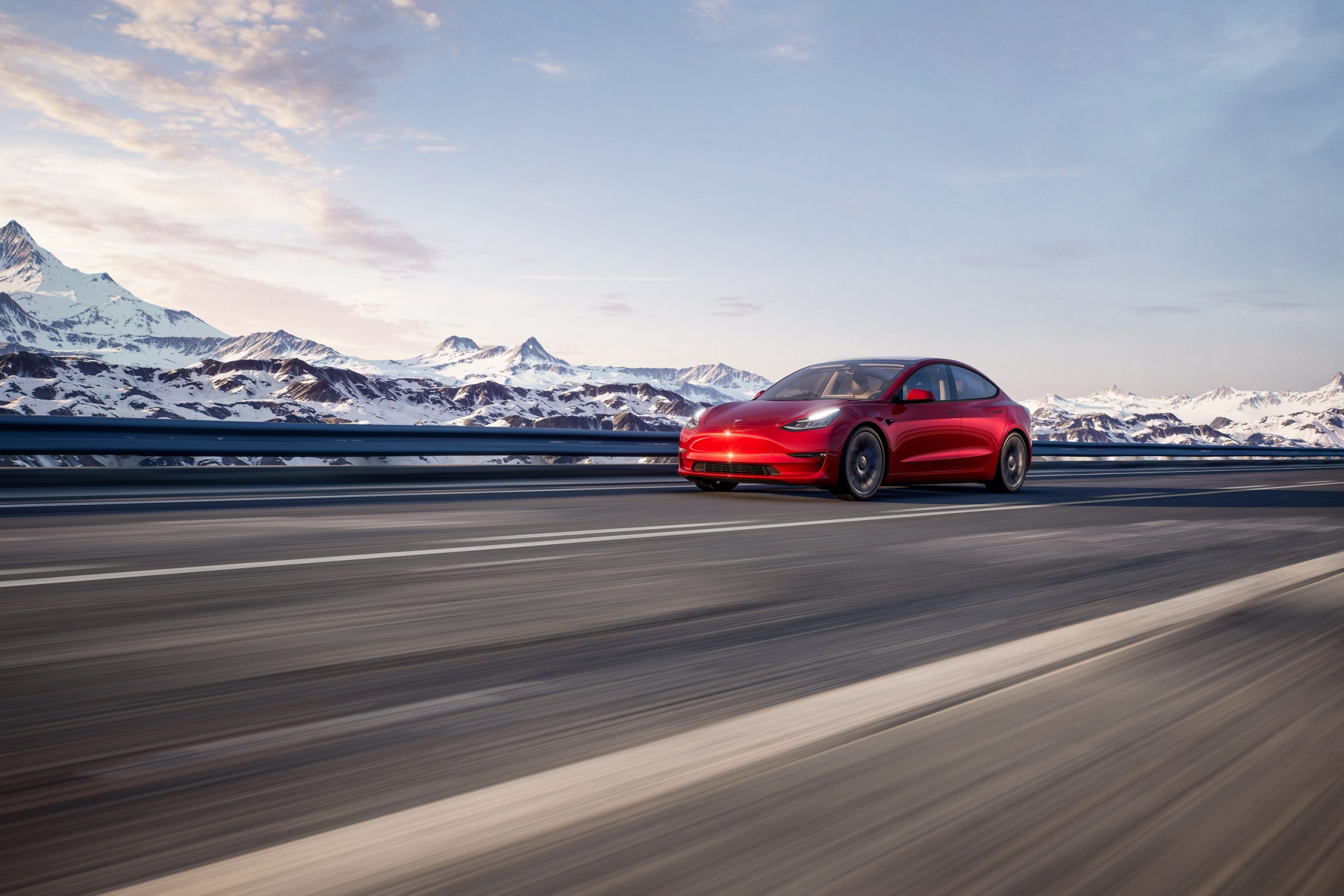 A red Tesla Model 3 shot from the front 3/4 on an alpine road
