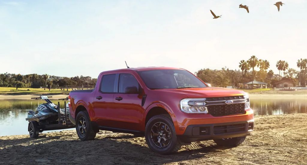 A red 2022 Ford Maverick compact pickup truck is towing two jetskis near a lake.