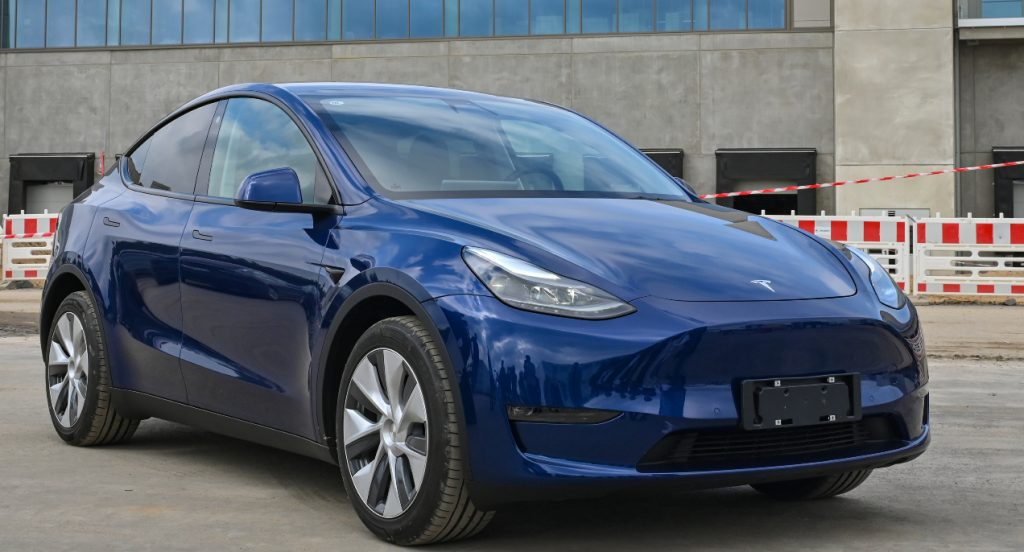 A Tesla Model Y in blue parked. A model just like this used Tesla's Sentry Mode to capture footage of an armed robbery