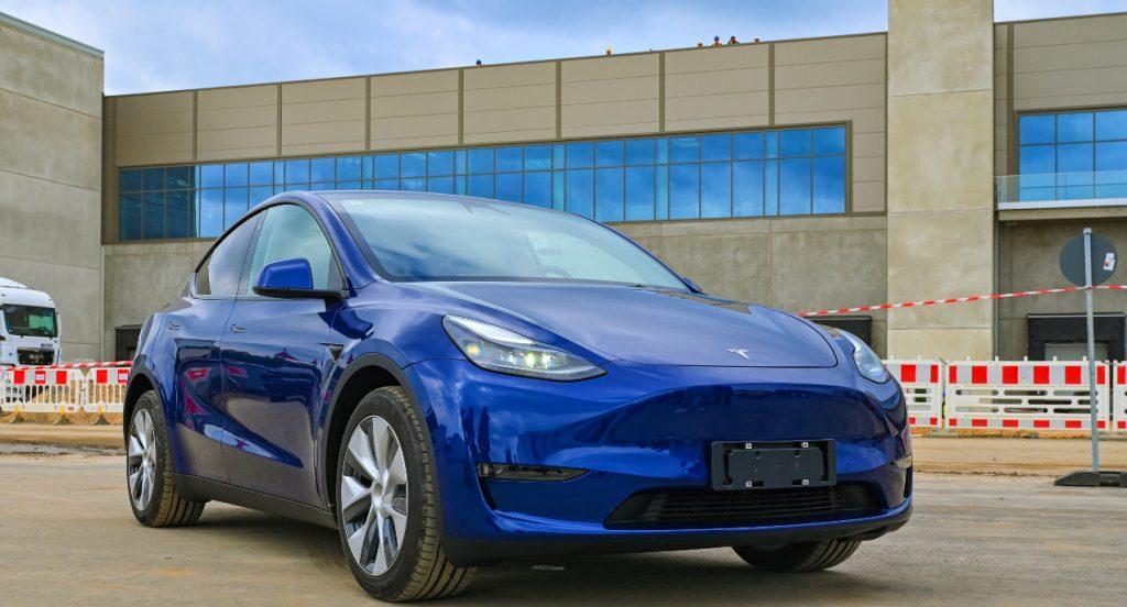 A blue Tesla model Y is parked.