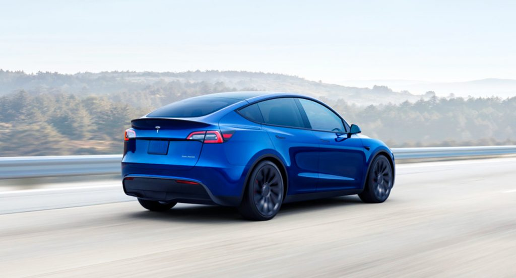 A blue Tesla Model Y electric crossover vehicle is driving on the road.