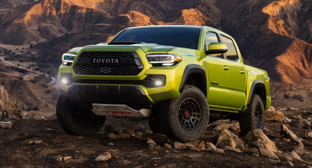 An Electric Lime Metallic 2022 Toyota Tacoma TRD Pro is driving over rocks.