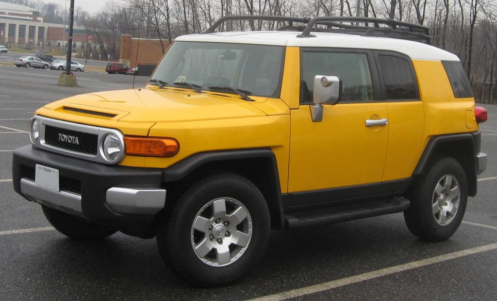 A discontinued yellow Toyota FJ Cruiser parked outside in a parking lot