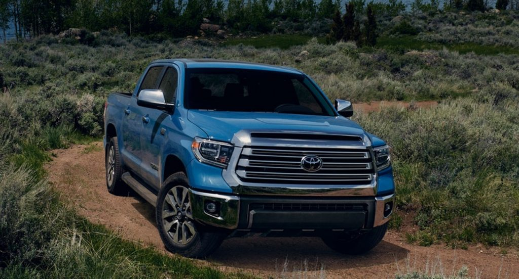 A blue Toyota Tundra is driving on a dirt road in nature.