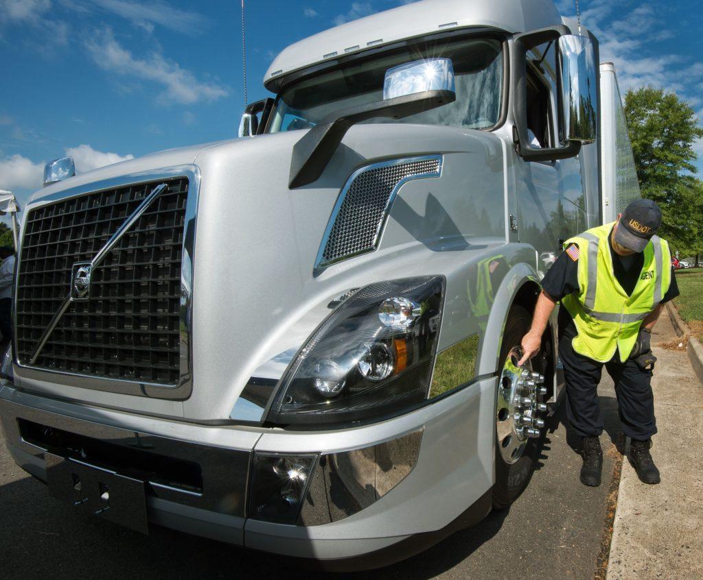 Trucker Inspects A Semi-Truck's Spiked Rim