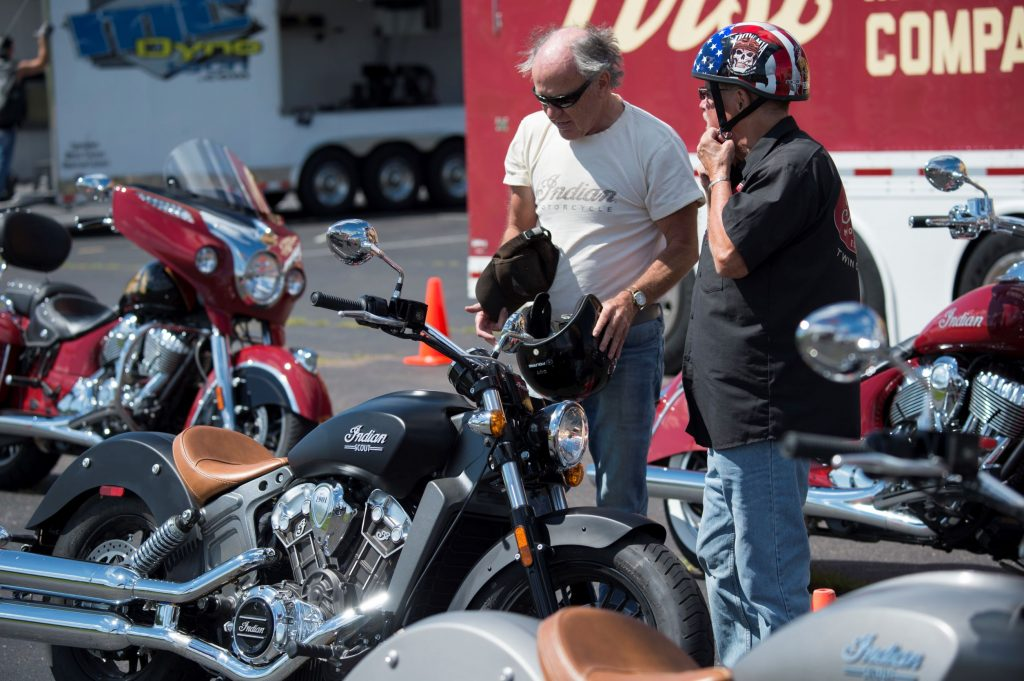 Two riders look at the motorcycles for sale at an Indian dealership